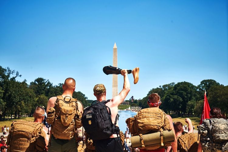 Rear View Of Tourist Holding Artificial Leg At Washington Monument Against Clear Blue Sky