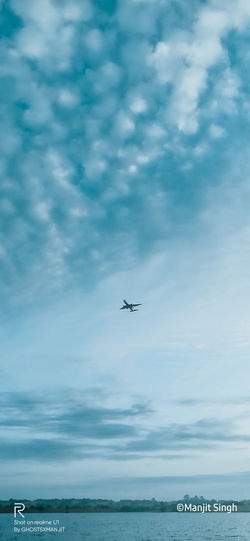 Airplane flying over sea against sky