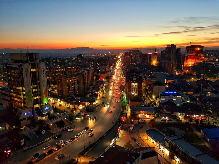 High angle view of illuminated city street and buildings against sky during sunset