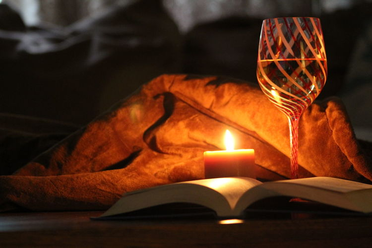 Close-up of illuminated candle and book in darkroom