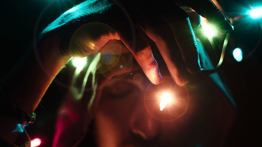 Cropped hand of young man holding illuminated string lights in darkroom