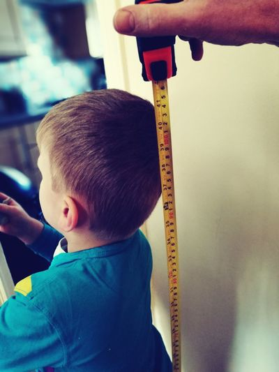 Cropped hand holding tape measure against boy at home