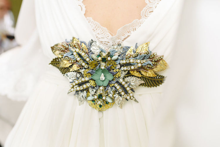 Midsection of bride with brooch