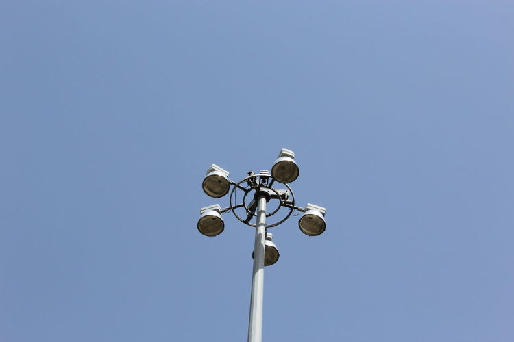Low angle view of street lights against clear blue sky