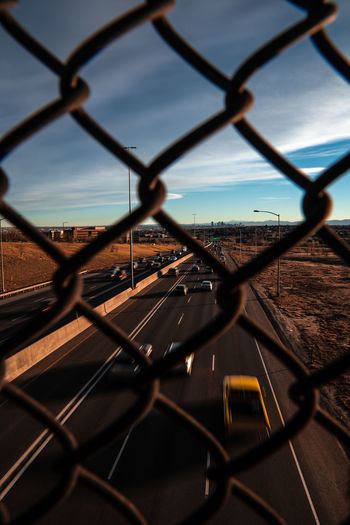 Highway view through fence Minimal Countryside Highway Destination Bokeh Auto Daylight POV Panorama Journey Safety White Interstate Rural Urban Chainlink Aerial Landscape Car Vehicle Trip Traffic Speed Fence Abstract Horizontal Daytime Driving Copy Space Road Freeway Travel Day Roadway Lane Art Transportation Above Blue Sky Design Background Superhighway Carriageway Trucks Architecture Transport Denver Colorado Rocky Mountains
