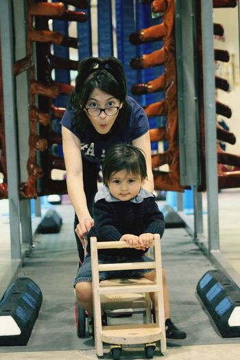 Portrait of girl pushing brother sitting on cart