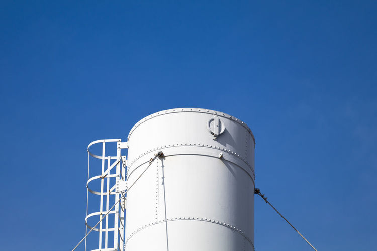 Low angle view of silo against clear blue sky