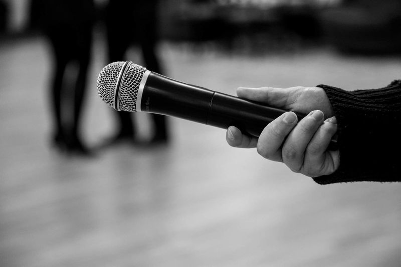 Close-Up Of Person Holding Microphone