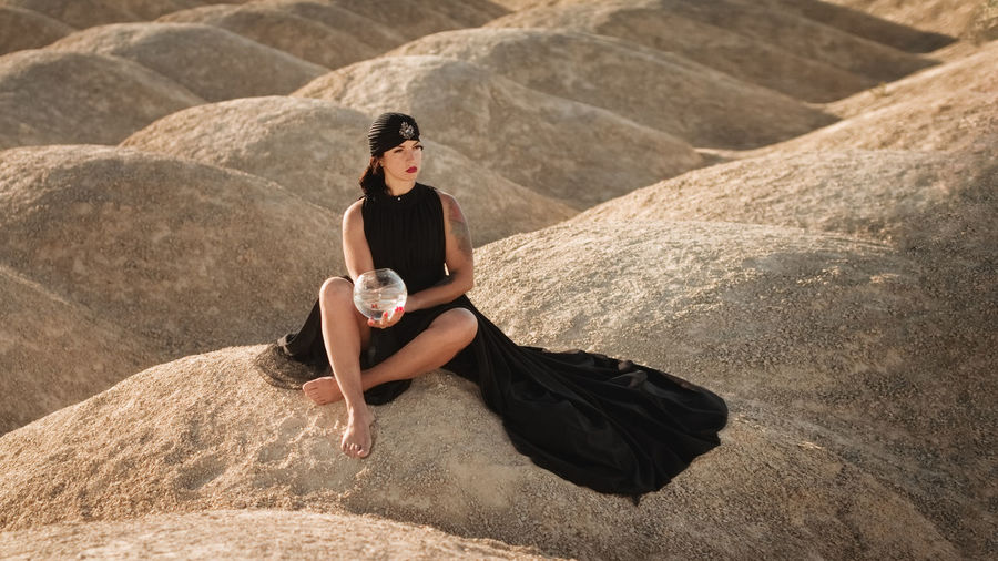 High angle view of woman sitting on rock