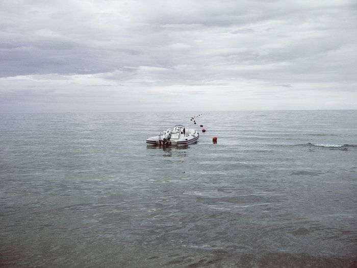 Boat Moored By Buoys On Sea Against Cloudy Sky