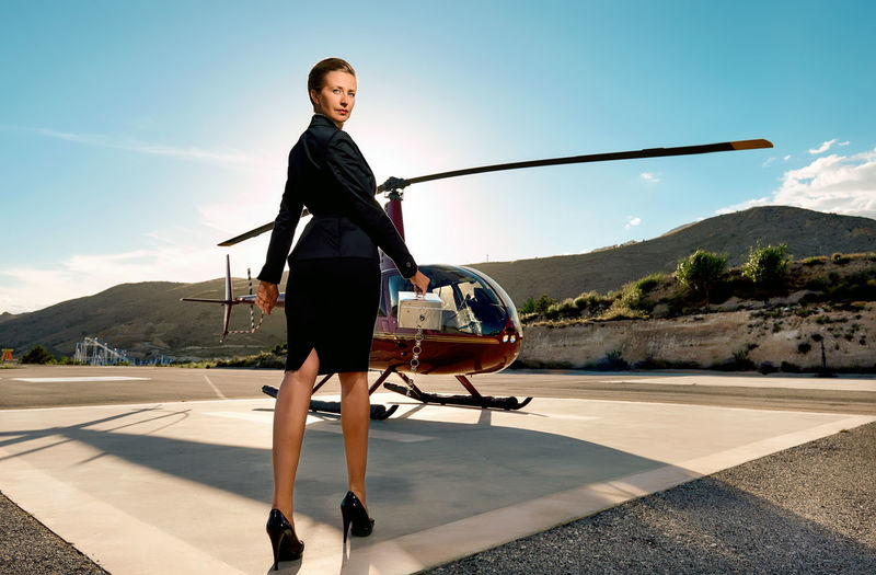Low angle portrait of businesswoman holding box while standing by helicopter during sunny day