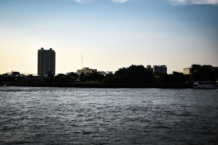 River by buildings in city against clear sky