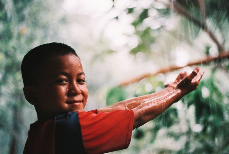Portrait of boy standing outdoors during rainy season