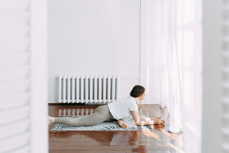 Side view of man sitting on wooden floor