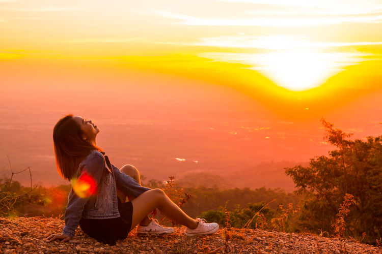 Side view of woman sitting against orange sky during sunset
