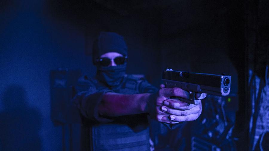Teenage boy aiming gun while standing indoors