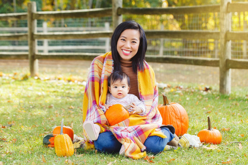 Portrait of mother with cute daughter sitting by pumpkins on land during autumn