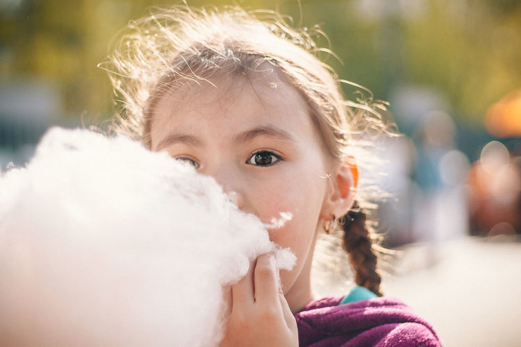 Close-up portrait of girl eating cotton candy