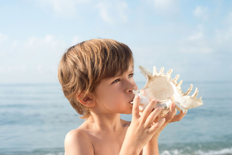 Close-up of shirtless boy holding seashell at beach