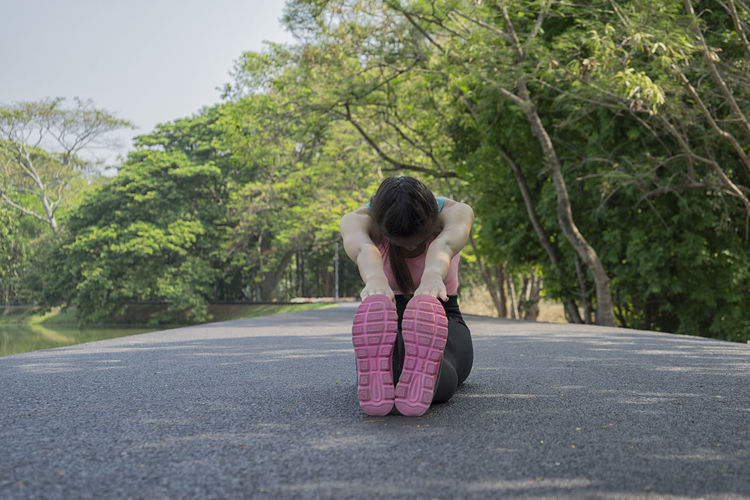 Woman stretching on road