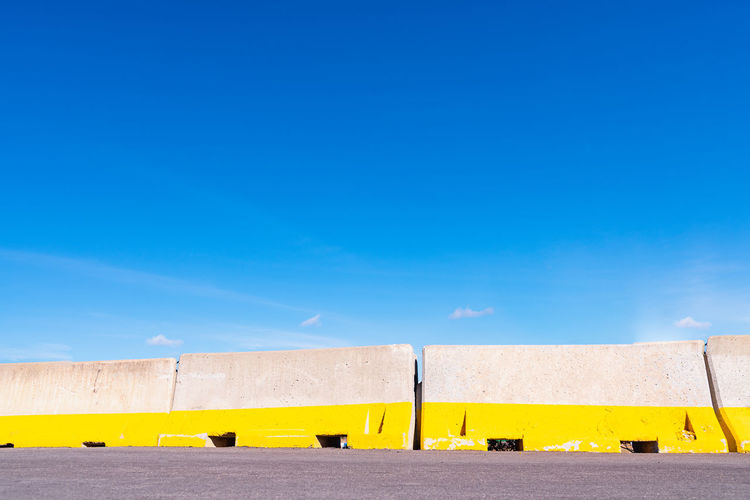 Low angle view of yellow flags against clear blue sky