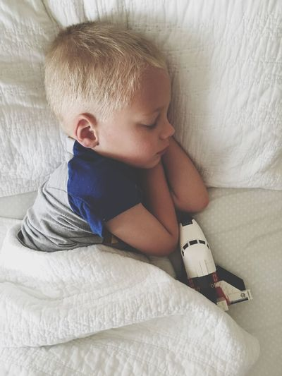 High Angle View Of Cute Boy Sleeping With Airplane Toy On Bed