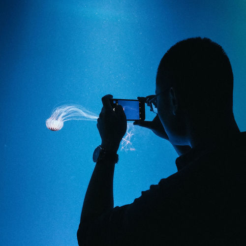 Man Photographing Jellyfish From Mobile Phone At Aquarium