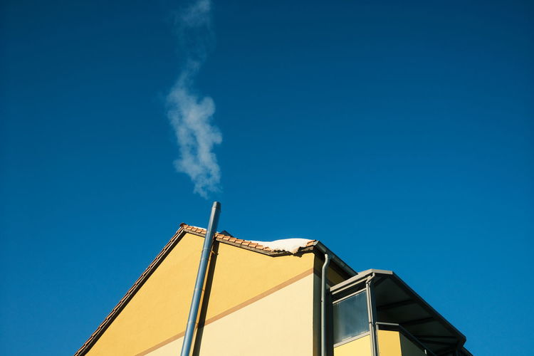 Low angle view of smoke emitting from chimney against clear blue sky