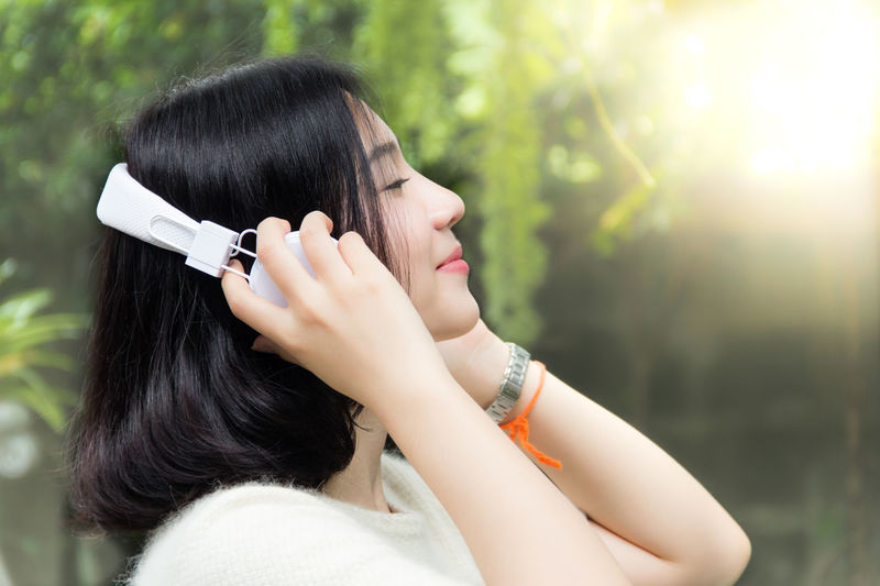 Side view of woman listening music on headphones