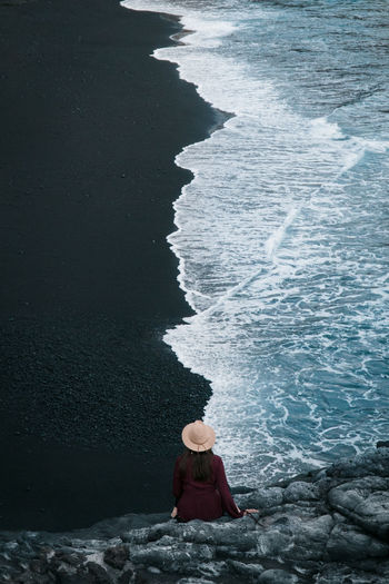 Fun with perspectives. Hat The Traveler - 2018 EyeEm Awards Adventure Beach Black Sand Beach High Angle View Land Nature One Person Outdoors Rear View Sea Sitting Water Waves The Great Outdoors - 2018 EyeEm Awards