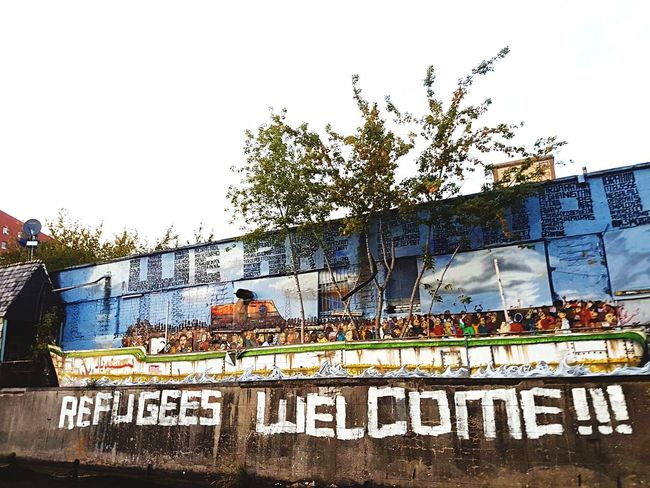Refugees welcome!!! EyeEm #FREIHEITBERLIN River Spree Capital City Refugeeswelcome Berlinstyle Germany Berlin Streetart We Are People Sky Communication Built Structure Building Exterior Outdoors The Street Photographer - 2018 EyeEm Awards Graffiti Tree