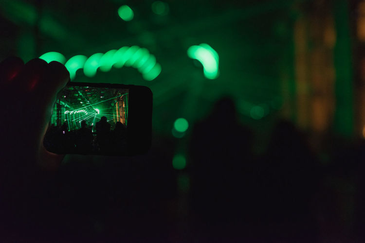 Man Photographing Entertainment Event With Smartphone At Night