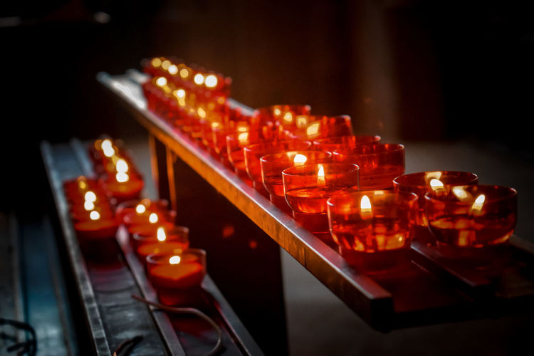red candles in a church Church Church Candles Red Candles Benches Light In The Darkness Illuminated Defocused Close-up Tea Light Lit Candlelight Flame Burning Candle Fire Wax Fire - Natural Phenomenon Building