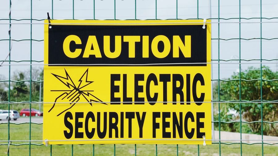 Close-Up Of Warning Sign On Electric Fence