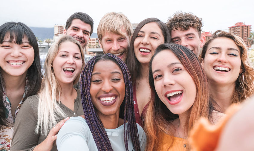 Multiracial millennial friends taking selfie with smartphone outdoor Young Millenials Millennials People Smiling Young Adult Group Of People Friendship Emotion Fun Women Teenager Selfie Multiracial  Camera