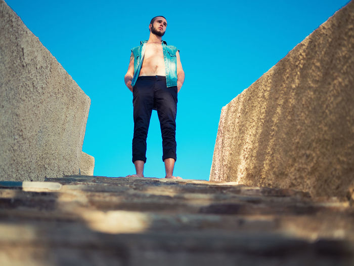 Architecture Between Blue Boy Casual Clothing Clear Sky Day Footpath Full Length Leisure Activity Low Angle View Person Portrait Sunlight Sunny Young Adult