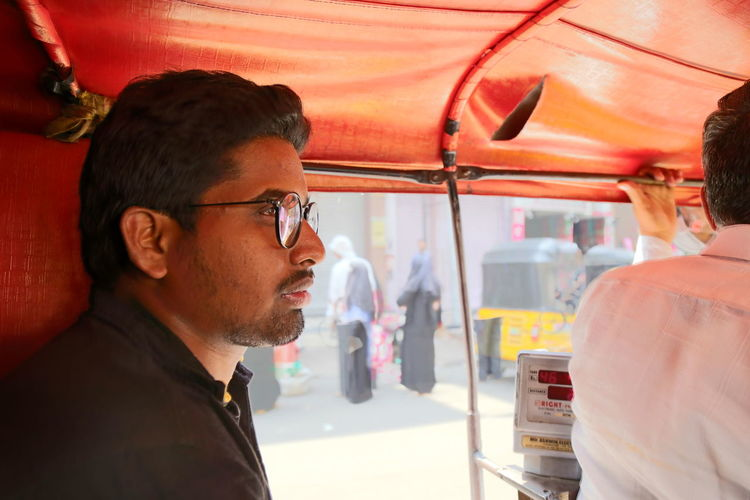 Thoughtful man by driver looking away while traveling in rickshaw