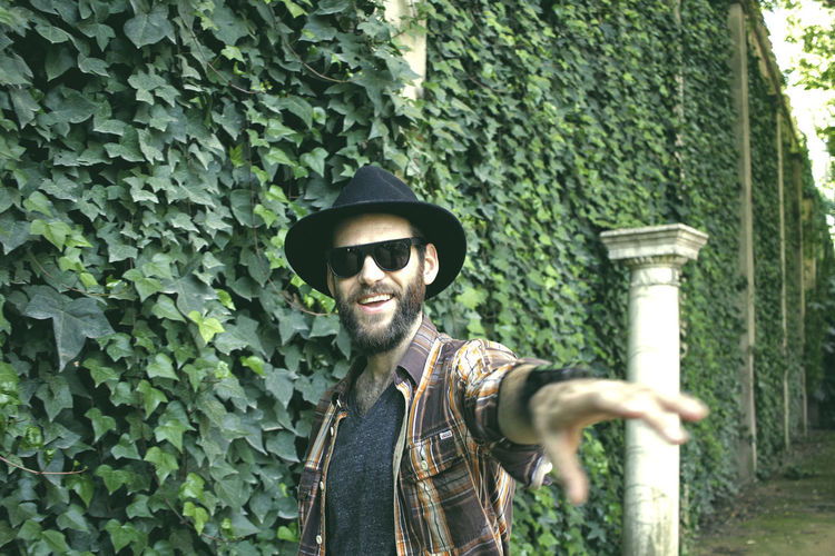 Bearded Man Standing Against Ivy