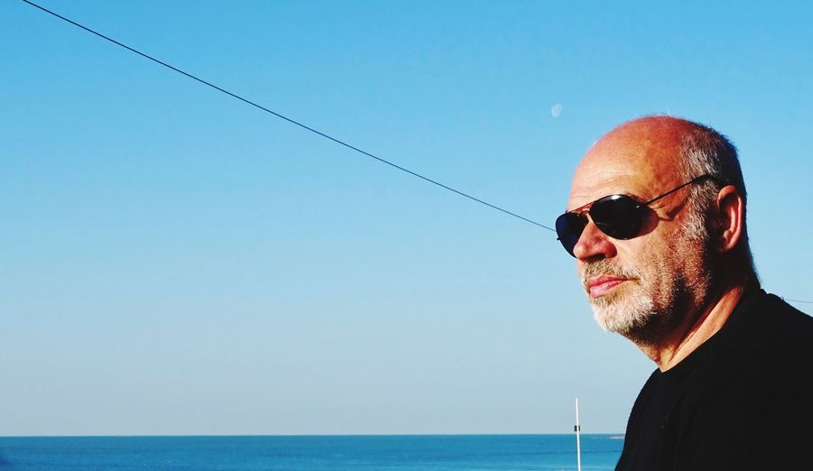Mature man wearing sunglasses looking at view against sea and clear sky