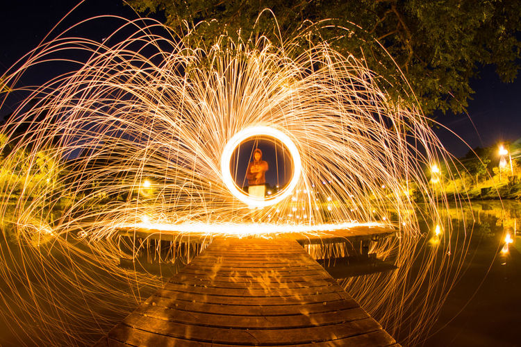 Man Spinning Wire Wool On Pier Over Lake At Night