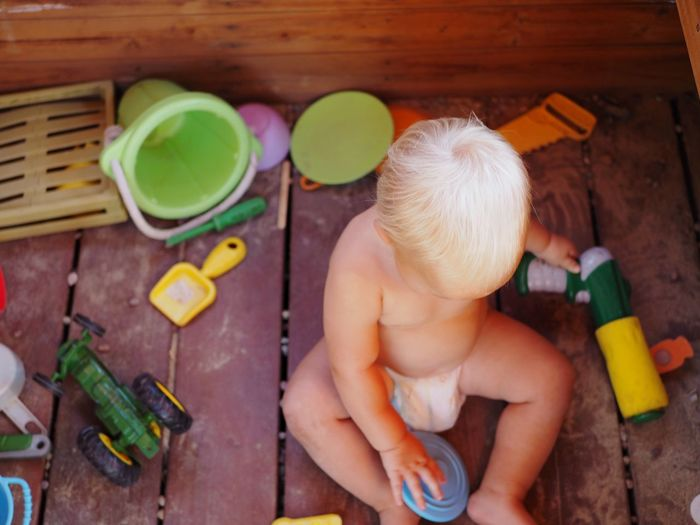 High angle view of boy playing with toys on floorboard