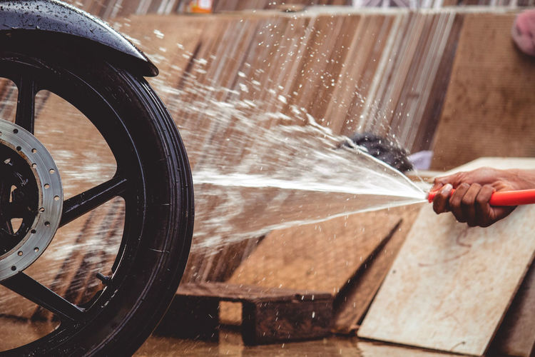 Cropped Hand Spraying Water On Motorcycle Tire