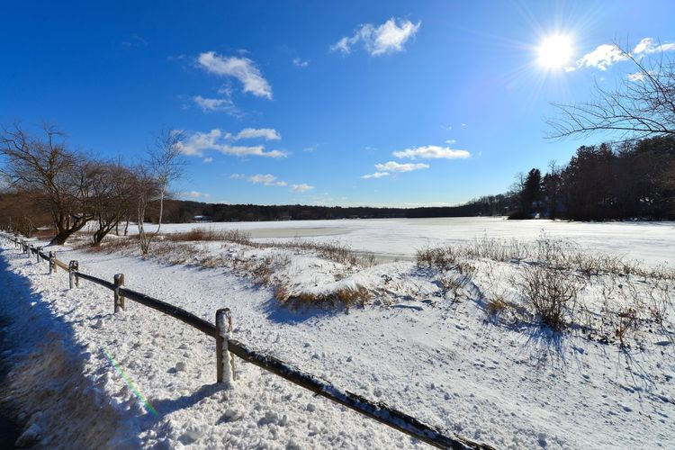 Scenic View Of Snow Covered Field Against Blue Sky