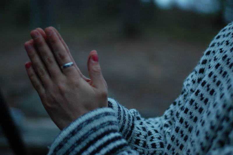 Midsection of woman with hands clasped standing outdoors