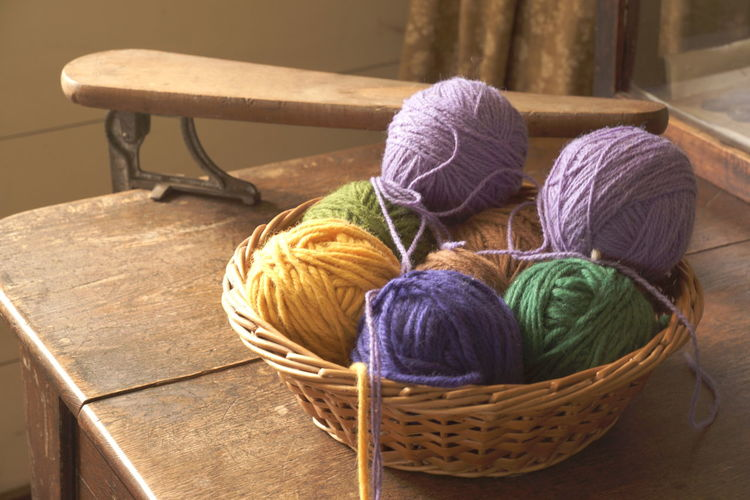 High Angle View Of Colorful Ball Of Wools In Container On Table