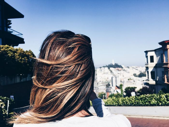 Rear View Of Woman With Brown Hair In City Against Sky On Windy Day