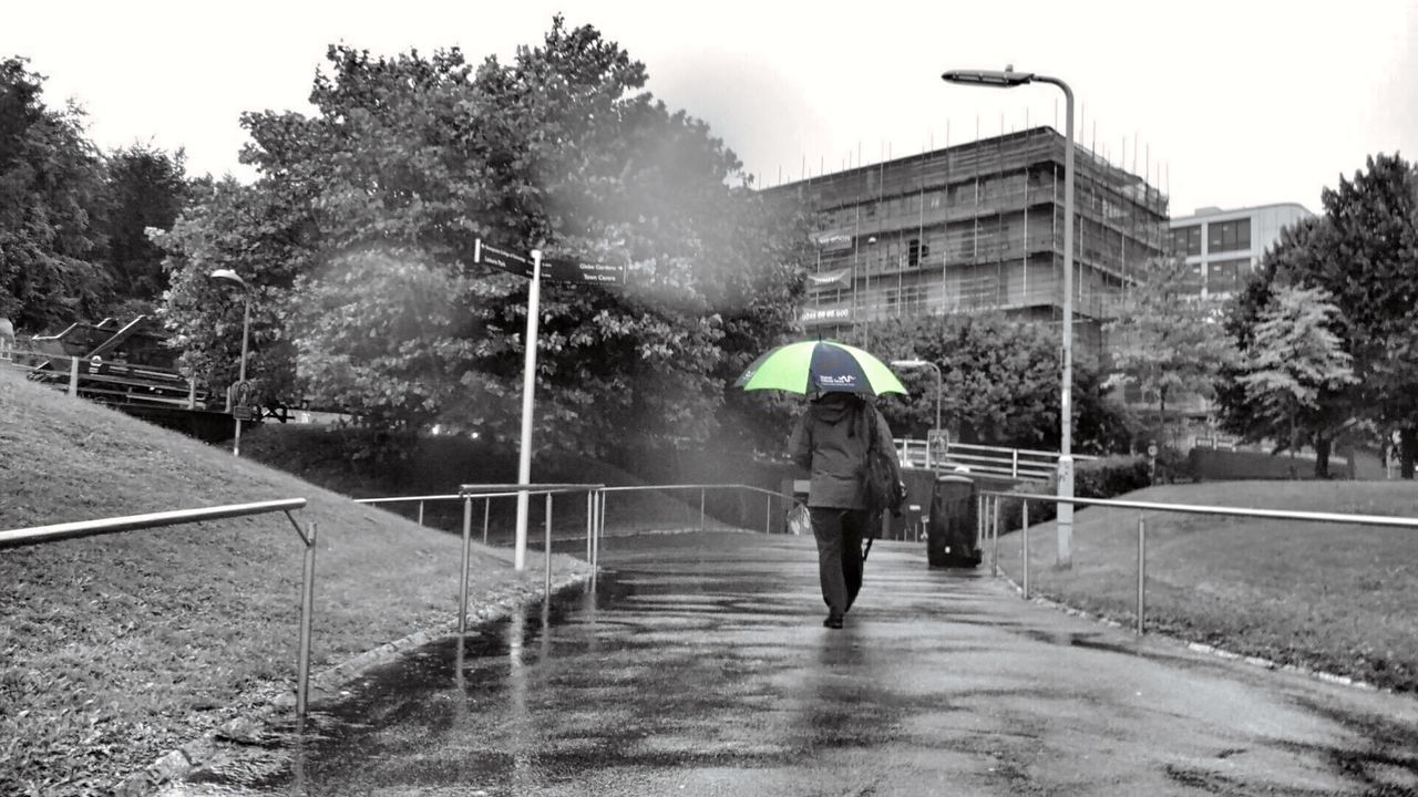 REAR VIEW OF MAN WALKING ON WET RAINY DAY