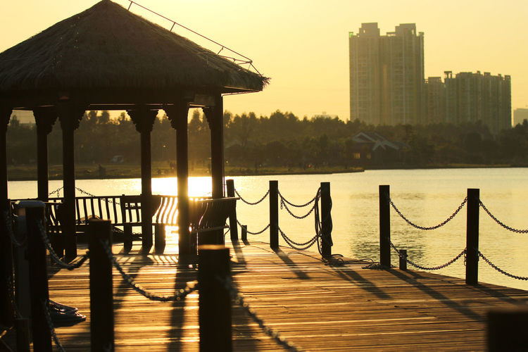 Wooden Pier In City Against Sky During Sunset