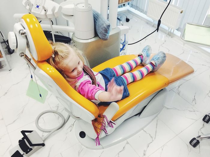 High angle view of girl waving hand while sitting on dentist chair