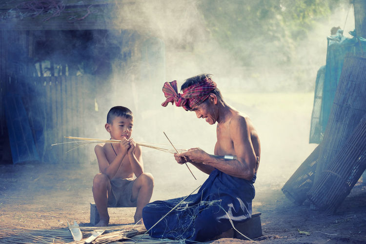 Shirtless Boy Looking At Craftsperson While Sitting On Ground